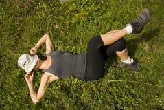 Fille détendant sur une herbe Image libre de droits