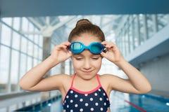 Fille déterminée ajustant des lunettes de natation images libres de droits