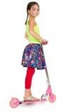 Fille d'âge primaire sur un scooter rose Images libres de droits