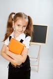 Fille d'école avec le livre jaune Photo stock