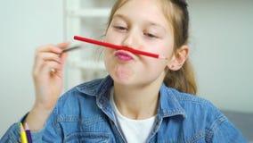 Fille d'école ayant l'amusement et faisant des visages avec les crayons colorés clips vidéos