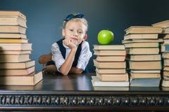 Fille d'école de plan rapproché s'asseyant à la table avec beaucoup de livres Images stock