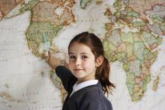Fille d'école indiquant l'Amérique sur une carte photographie stock libre de droits