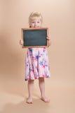 Fille d'école maternelle tenant le tableau Images stock