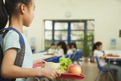 Fille d'école tenant le plateau de nourriture dans la cafétéria de l'école Image stock