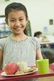 Fille d'école tenant le plateau de nourriture dans la cafétéria de l'école Photos stock
