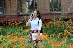 Fille d'écolière avec de longs cheveux dans l'uniforme scolaire parlant au téléphone photo stock