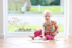 Fille d'élève du cours préparatoire jouant avec des puzzles sur le plancher Image libre de droits