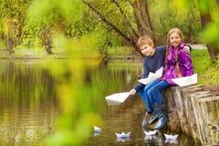 Fille d'étreinte de garçon près de l'étang mettant les bateaux de papier Image stock