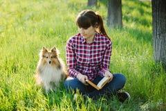Fille d'étudiant apprenant en nature avec le chien Photo libre de droits
