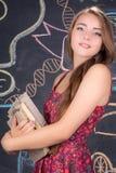 Fille d'étudiant avec des supports de livres devant le tableau noir d'école Photo stock