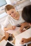 Fille d'étudiant dans la classe fonctionnant avec des collègues Images stock