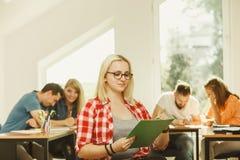 Fille d'étudiant devant ses compagnons dans la salle de classe Images stock