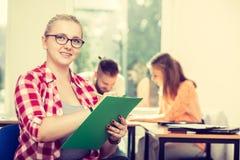 Fille d'étudiant devant ses compagnons dans la salle de classe Image stock