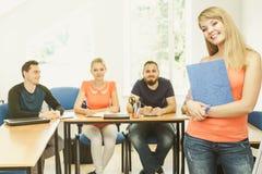 Fille d'étudiant devant ses compagnons dans la salle de classe Photographie stock