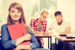 Fille d'étudiant devant ses compagnons dans la salle de classe Photo stock