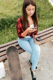 Fille d'adolescent d'été s'asseyant sur un banc, tenant un smartphone dans des ses mains, et une tasse de café photo libre de droits