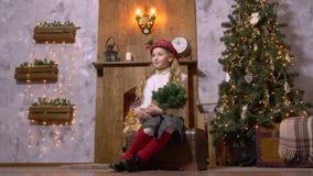 Fille d'adolescent avec des branches de sapin posant près de l'arbre de Noël dans le studio de photo clips vidéos