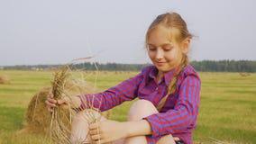 Fille d'adolescent avec la guirlande de paille sur le fond de pile de foin Guirlande de port de paille de fille heureuse sur mois clips vidéos