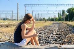 Fille d'adolescent avec la séance mobile sur la voie ferroviaire non finie Photo stock