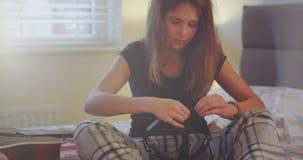 Fille d'adolescent dans des pyjamas sur sa chambre à coucher préparant pour porter des lunettes d'une réalité virtuelle, plan rap banque de vidéos