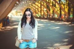Fille d'adolescent dans des shorts et des lunettes de soleil de denim Images libres de droits