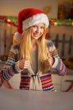 Fille d'adolescent dans le chapeau de Santa montrant des pouces  Image stock
