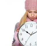 Fille d'adolescent dans le chapeau et l'écharpe d'hiver montrant l'horloge Photo libre de droits