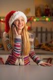 Fille d'adolescent dans le téléphone portable parlant de chapeau de Santa Photographie stock