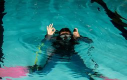 Fille d'adolescent de piscine de cours de plongée à l'air avec l'instructeur Images stock
