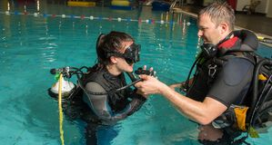 Fille d'adolescent de piscine de cours de plongée à l'air avec l'instructeur dans l'eau Images stock