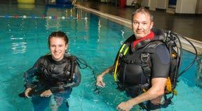 Fille d'adolescent de piscine de cours de plongée à l'air avec l'instructeur dans l'eau Photos stock