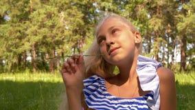 Fille d'adolescent de portrait avec la lame d'herbe dans des mains sur le pré d'été Fille mignonne tenant la paille d'herbe verte banque de vidéos