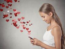 Fille d'adolescent employant le service de mini-messages au téléphone intelligent Images libres de droits