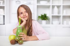 Fille d'adolescent rêvassant avec un jus de fruit vert frais images libres de droits