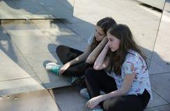 Fille d'adolescent reflétée dans le miroir avec un visage triste se reposant en position de lotus dans le parc photographie stock libre de droits
