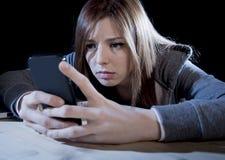 Fille d'adolescent semblant inquiétée et désespérée au téléphone portable comme l'Internet a égrappé l'effort cyberbullying maltr Photo stock