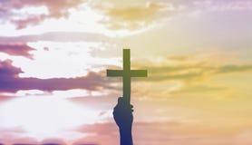 Fille d'adolescent tenant la croix à disposition pendant le beau coucher du soleil Mains pli?es dans le concept de pri?re pour la photographie stock