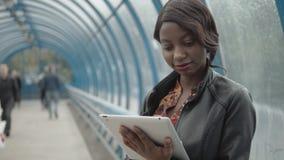 Fille d'afro-américain, étudiant travaillant avec son comprimé dans la rue, rue de ville, souterrain, fin heureuse  banque de vidéos