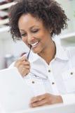 Fille d'Afro-américain de métis à l'aide de la tablette photo libre de droits