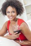 Fille d'Afro-américain de métis buvant du vin rouge Images stock