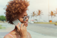 Fille d'afro-américain invitant le smartphone Photo stock