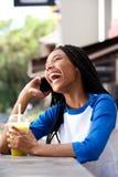 Fille d'afro-américain parlant au téléphone portable et riant du café Images stock