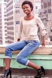Fille d'Afro-américain s'asseyant sur le dessus de toit Photographie stock libre de droits
