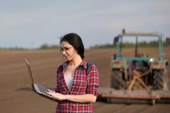 Fille d'agriculteur avec l'ordinateur portable dans le domaine avec le tracteur Image libre de droits