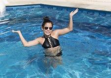 Fille d'Amerasian de douze ans ayant l'amusement dans la piscine Photo libre de droits