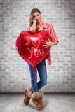Fille d'amour étreignant le grand coeur rouge Image libre de droits