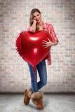 Fille d'amour étreignant le grand coeur rouge Photo libre de droits