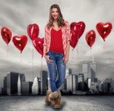 Fille d'amour se tenant entre beaucoup de ballons rouges Image libre de droits