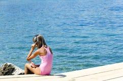 Fille d'Appy avec des écouteurs se reposant sur la couchette de rivière et écoutant la musique à l'été Photographie stock libre de droits